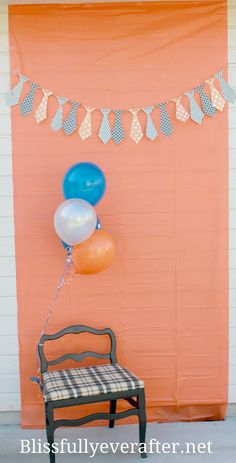 This was our DIY photobooth we made out of a plastic table cloth hung on the wall with a DIY tie banner layered over the top of it. I brought out a chair from the house and tied some balloons around it to create a fun backdrop to take goofy pictures!