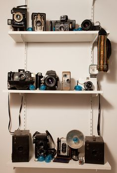 Camera collection display...love the smattering of blue bulbs!