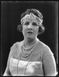Georgina Leonora Douglas, nee Mosselmans, Marchioness of Queensberry, 1922; wearing a fabulous diamond pearl and emerald tiara. Featuring at least five diamond and pearl lacey panels flanking a central downward-pointing diamond anthemion, topped with a large emerald