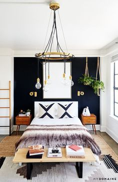Bedroom with a dramatic exposed wire chandelier, matching gold sconces on a black contrast wall, and layered rugs