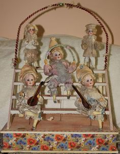 Beautiful German mechanical music box / Automaton with 5 bisque headed dolls.Glass eyes, Mohair Hair, original clothing, hands & feet are carved wood. All dolls move when handle is turned & music played.  $836.OBO/Sold Oct.26, 2015
