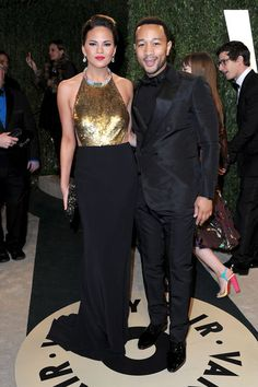 Chrissy Teigen in a black-and-gold embellished gown at the Vanity Fair #oscars party.