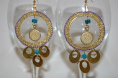Esmeralda's Sister - ML168E  #Earrings #Jewelry #Accessories #TelAviv   Spice up your life with these exotic gypsy earrings that make you want to belly dance. The metal coin-style beads hanging from the bottom soothe you with soft wind-chime music as you move. Purple thread and metallic gold fabric thread crocheted around a metal ring. Turquoise stones. Gold-plated coin-style bead hanging in center of circle, gold-plated earring base.  $57.00