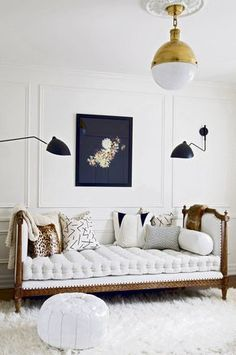 tufted white mattress + throw cushions on single french bed turned into a day bed with with a set of carbonised steel flex-arm wall lights flanking the bed.