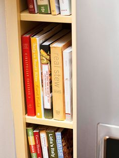 Carve out a niche for cookbooks in a sliver of space next to a refrigerator. Organize cookbooks by category on each shelf./