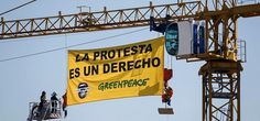 """Greenpeace activists display a banner reading """"Protest is a right"""" as they hung from a crane to protest against the Public Security Law above the Parliament in Madrid, Spain, Tuesday, June 30, 2015.  Photo:Reuters"""