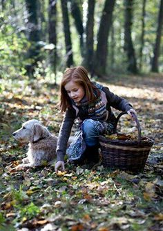 ...cute little girl gathers leaves, with her dog at her side....