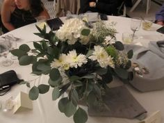 Lovely centerpiece made from flowers and greenery purchased from Sam's Club. The bride bought Hydrangea - White - 20 Stems  and Assorted Greenery - 8 Bunches. You could easily make 12 centerpieces with that purchase.