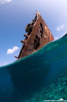 Navio antigo naufragado, parcialmente fora da água, e o mar abaixo da superfície. Foto de Christian Loader.