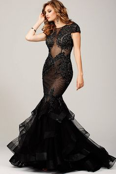 Long sheer black gown with cap sleeves features jeweled embellishments, a tiered skirt with embellished edges, and a button up backside.
