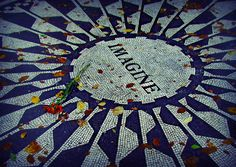 """The 'Strawberry Fields' memorial, in Central Park, is a triangular piece of land falling away on the two sides of the park. The focal point is a circular pathway mosaic of inlaid stones, with a single word, the title of Lennon's famous song... """"Imagine""""."""