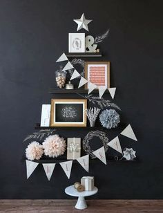 black wall, Christmas tree made from shelves, bunting banner, cake stand