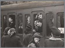 rukte op een perron van het Centraal Station bij een vertrekkende trein, waarin zich vermoedelijk voor tewerkstelling in Nederlandse rijkswerkkampen opgeroepen joodse mensen bevinden. liopuiouiop