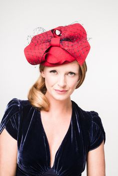 Fiona A red felt beret style headpiece adorned with a hand sculpted bow and finished with ornate navy veiling.  A timeless and classic design you will wear time and time again.
