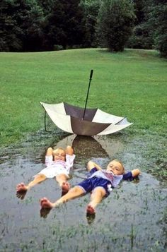 Love A Rainy Day. Kids lying in a mud puddle, water puddle actually ditched the umbrella for fun, so cute! I Love Rain, Rain Dance, Under My Umbrella, Rain Umbrella, Singing In The Rain, Baby Kind, Beautiful Children, Little People, Rainy Days