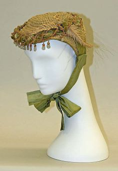 Green straw bonnet with artificial ferns, tasseled velvet and cord trim, and green silk ties, probably American, 1864-67.