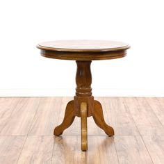 This end table is featured in a solid wood with a glossy medium oak finish. This side table has a round table top, a carved pedestal base and curved legs. Perfect as a large plant stand!  #americantraditional #tables #endtable #sandiegovintage #vintagefurniture