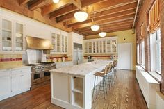 The Kitchen -   boasts an exposed beam ceiling, marble island, stainless-steel appliances, and glass-front cabinetry.