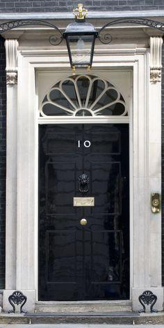 Black door, 10 downing street London Real door hardware painted black to blend with door--- gold knobs in center