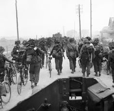 British troops from 3rd Division, some walking with bicycles, move inland from Sword Beach; June 6, 1944.