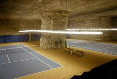 Underground Racquets Ltd., Carthage, MO.   This two-court facility is located inside the blasted-out caves of AmeriCold Logistics, Inc., a food distribution services company that uses the nearly 43.5 million cubic feet of underground caves for food storage and office space.  Find on Juump at http://www.juump.com/places/underground-racquets-ltd