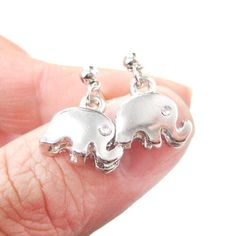 A pair of small elephant shaped stud dangle earrings in silver with small rhinestone eyes! Small, cute and pretty!  ---  Size: 1.5 cm tall by 1 cm wide and comes with earring backs!  Material: Silver Plated Tin Alloy  Handling time: - Please allow two to three business days for us to process