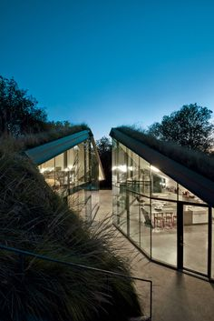 Edgeland House, built on a cliff-top lot in Austin by architect Thomas Bercy for lawyer and writer Chris Brown, is topped by a living roof to help it blend into the landscape. The concrete, steel, and glass house is divided into two distinct public and private halves.