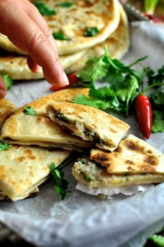 Hand reaching in to take a pice of Aloo Paratha (Indian Potato Stuffed Flatbreads) filled with mashed potato and spiced beef.