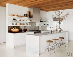 kitchen, open shelving, white cabinets, white dishes, cherry blossoms, branches, carrera marble