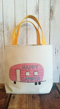 Handmade canvas tote lined with very retro camping fabric and cotton yellow webbing handles.Original Camper artwork adorns the front with Happy Camper . Made for your little one to tote all their essentials to take with them for their camping weekend! Made of a durable canvas to withstand lots of play.  If you prefer a different color for the camper,please leave in message to seller upon checkout.  11.5 H x11.5 W with a gusseted bottom 12 handles (all measurements are approximate,they are…