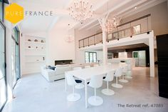 Modern open plan dining/kitchen/living room all in white with fabulous chandeliers. This barn convention can be rented to sleep 10 people from Pure France. Click the image to see photos.