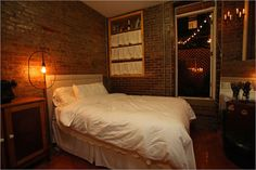this bedroom is so cozy and I'm all about the exposed brick. not too fussy.