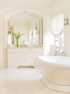 """Dreamy White """"Ivory and white tile floors coordinate with creamy walls to create a space lovely in its simplicity. A large arched mirror crowned with white trim both expands and adds architectural value to this bathroom, while a stately freestanding tub and vintage faucet complete the elegant look."""" The mirror is the highlight to this design for me."""