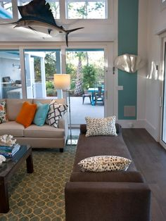 This coastal living room at the HGTV Smart Home 2013 located in Jacksonville, FL features a swordfish hanging decor as the centerpiece. Seashell decor accents the gray plush sofa and throw pillows. The  overall blue color scheme enhances the coastal style room.