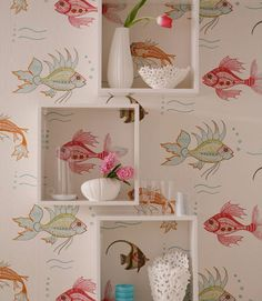 La carta da parati con dipinti dei pesci, sommata alle mensole con gli oggetti in tema marino, danno l'idea di un acquario in casa. La tappezzeria è di Nina Campbell.