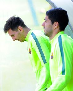 Lionel Messi (L) and Luis Suarez of FC Barcelona walk onto the pitch prior a training session ahead of theid UEFA Champions League round of 16 match against Manchester City at Ciutat Esportiva on March 17, 2015 in Barcelona, Catalonia.