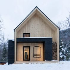 Canadian studio Cargo Architecture used a restrained materials palette for this woodland vacation cottage, which has a swing seat and a wood store built into its facade.