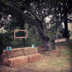 """""""Redneck"""" photo booth so guests could take pictures for us to put in the guestbook.  Hay bale seating, DIY sign, and Antique picture frame. So inexpensive and fun!"""