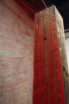 Red Thread Legend Series . Beili Liu . Two weathered, human-sized oak columns (reclaimed wood from shipping containers) with thousands of gossamer red threads spanning the distance between them. Each thread is held in place by a needle.