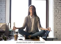 Serene calm business woman sit on office desk taking break for meditation, mindful employee doing yoga exercise in lotus pose for relaxation at workplace, no stress relief, balance at work concept  photo Royalty free images stock