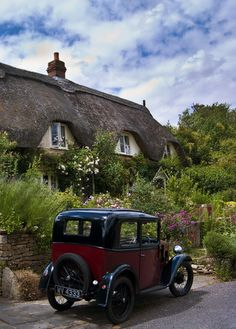 Thatched cottage and vintage car in Lacock, Wiltshire, England.