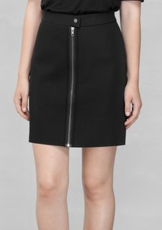 Made from a sturdy scooba-looking material with a raw hem, this skirt features a chunky zip and button-closure.