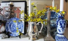 Vignette of blue and white china with yellow Forsythia on mantelpiece (Jenny Mein's living room)