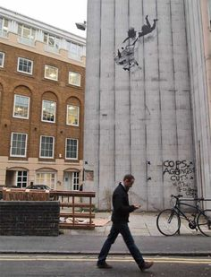 Banksy: Well-timed photo of this mural, as the passer-by carries on walking, oblivious...