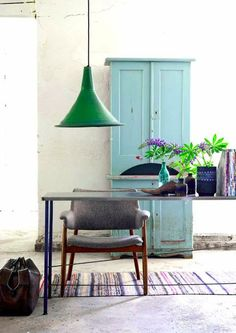 The concrete floors, the green pendant lamp and the blue armoire play of each other beautifully.