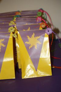 Rapunzel party bags - easy to copy. Yellow bag, purple banner, purple bow, glitter rapunzel braid