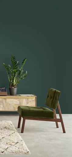 The Aron chair in fern velvet. Inspired by a vintage mid-century piece that caught our designer's eye, the Aron features an exposed frame that makes it a statement piece, while a low design and generous cushions make it ideal for lounging.