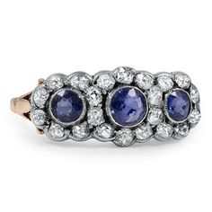 A beautiful example of Victorian-era artistry, this romantic ring features three round natural sapphires in milgrain-embellished bezel settings. All are encircled by glittering diamond accents to create a feminine floral design (approx. 0.66 total carat weight).