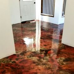 Painted concrete floor. I took black concrete paint and covered the concrete floor. Bought some metallic paint watered it down, sloshed it on my black floor and then used the air compressor to blow the colors around. Let dry and varithane 4 or 5 times. VA walla acid wash looking floors without the $$$$.