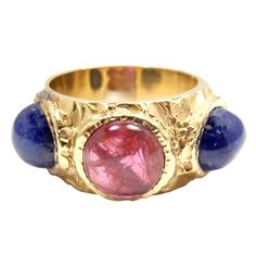 18k Yellow Gold Cabochon Sapphire & Ruby Ring by Bulgari. With two round cabochon sapphires. Total sapphire weight: 6CT. And one round cabochon ruby, total weight: 3CT. Circa 1990s
